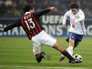Manchester United's Brazilian player Fabio (R) fights for the ball with AC Milan's defender Alessandro Nesta during their UEFA Champions League round of 16 match on February 16, 2010 at San Siro stadium in Milan. Manchester United defeated AC Milan 3-2. AFP PHOTO / Damien Meyer (Photo credit should read DAMIEN MEYER/AFP/Getty Images)